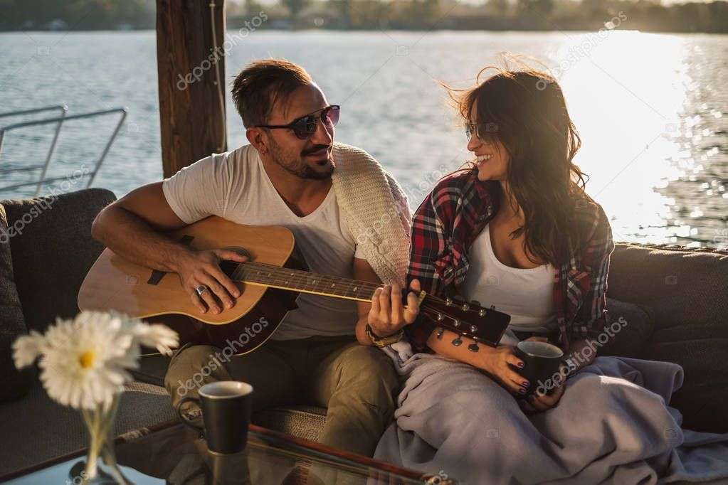 Man playing guitar for his girlfriend by the river while she is smiling. Beautiful sunset