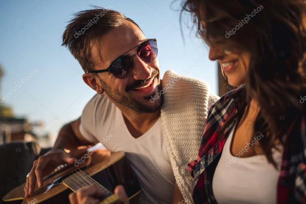 Man playing guitar for his girlfriend and smiling. Beautiful sunny day