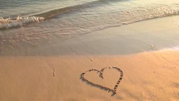 Eine herzförmige Zeichnung auf dem Sand wird von der Meereswelle weggespült. Küste bei Sonnenuntergang.