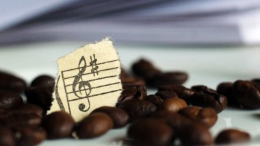 Guitar strings, torn paper notes and coffee beans, music
