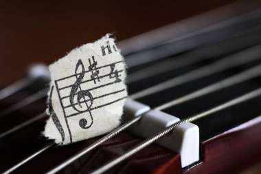 Guitar strings and torn paper notes, music