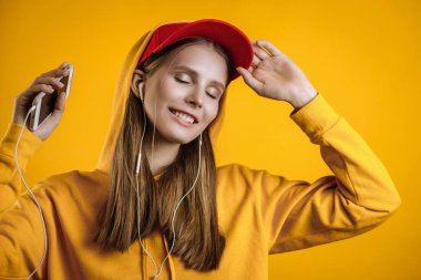 beautiful girl listening to music on headphones, photo in studio on yellow background