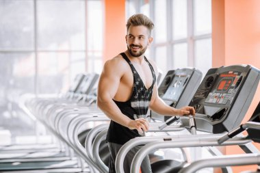 handsome pumped man runs on a treadmill in the gym
