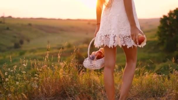 schöne sexy blonde Mädchen in weißem Kleid posiert in einem Feld bei Sonnenuntergang mit einem Korb voller Früchte