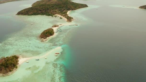 Kis torpic sziget fehér homokos stranddal, felülnézet.