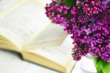 Lilac and a book. A bouquet of spring flowers against the background of an open book lying on a white wooden surface.