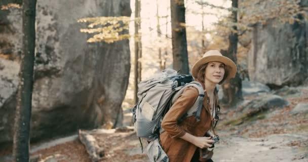 aktive gesunde kaukasische Frau beim Fotografieren mit einer Vintage-Filmkamera auf einem Waldfelsen