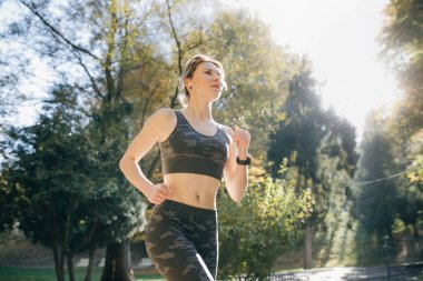 Portrait of attractive brunette female runner running in city park airpods bluetooth headphones earphones. Healthy fitness athletic woman jogging outdoors