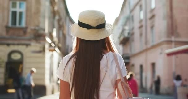 Trendy student in fedora hat, round glasses and hipster backpack. Close up view of Pretty Young Woman Walking like a Model. Looking at the Camera. Wearing Stylish Straw Hat. Having Elegant Make up.