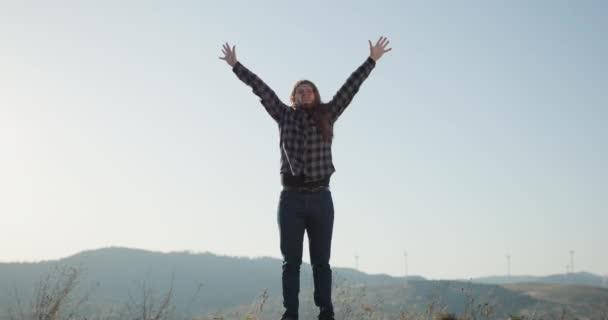 Muž zvedne ruce, když stojí na vrcholu hory při západu slunce. Úspěch a úspěch - šťastný muž slaví. Mladý městský profesionální úspěšný muž dostávající dobré zprávy.