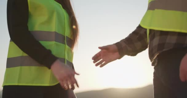 Two businessmen engineers shaking hands. Two engineers in hardhats shake hands. Close-up of the Businesswoman and Businessman Shaking Hands