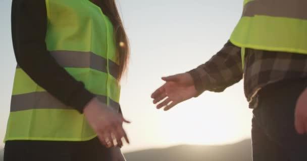 Dva podnikatelé si potřásají rukama. Dva inženýři v přiléhavých čepicích si podávají ruce. Detailní záběr Podnikatelka a Podnikatel třesoucí se ruce