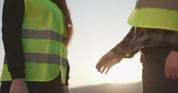 Nesoustředěná podnikatelka si potřásá rukou s podnikatelem. Ruce nad hlavu. Dokončení dohody a uzavření smlouvy potřesením rukou. Nízký pohled na ruce dvou inženýrů potřásajících si rukou.