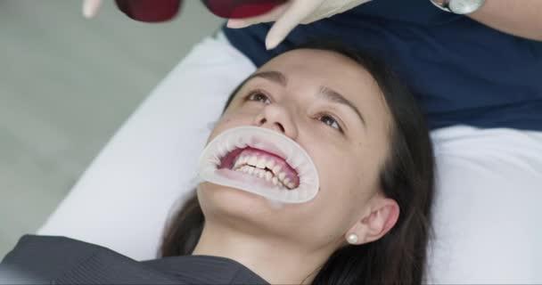 Die Kundin einer Klinik sitzt mit offenem Mund im Zahnarztstuhl und trägt eine orangefarbene Schutzbrille. Zahnarztpraxis. Zahnmedizin. Stomatologie