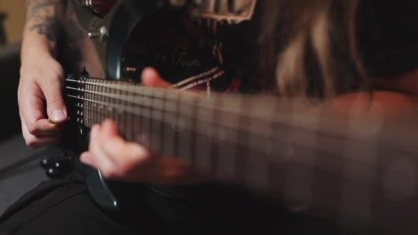 Lidské ruce hrající na elektrickou kytaru. Detailní záběr rockového hudebníka hrajícího na kytaru s malebným osvětlením. Muž hrající na elektrickou kytaru. Prsty na strunách kytary.