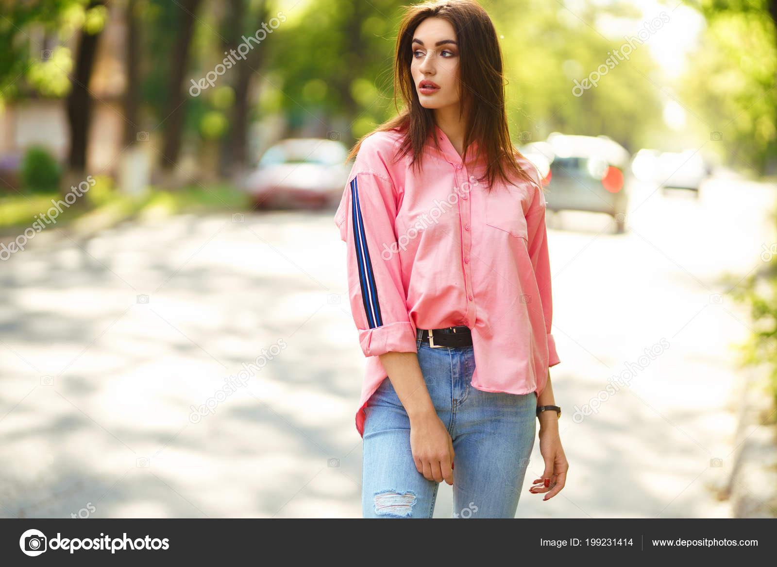 e6374eee2 Retrato de uma jovem e bela mulher em roupas casuais na rua. vestida de  jeans e uma camisa-de-rosa. conceito de primavera   verão. hora de relaxar.  garota ...