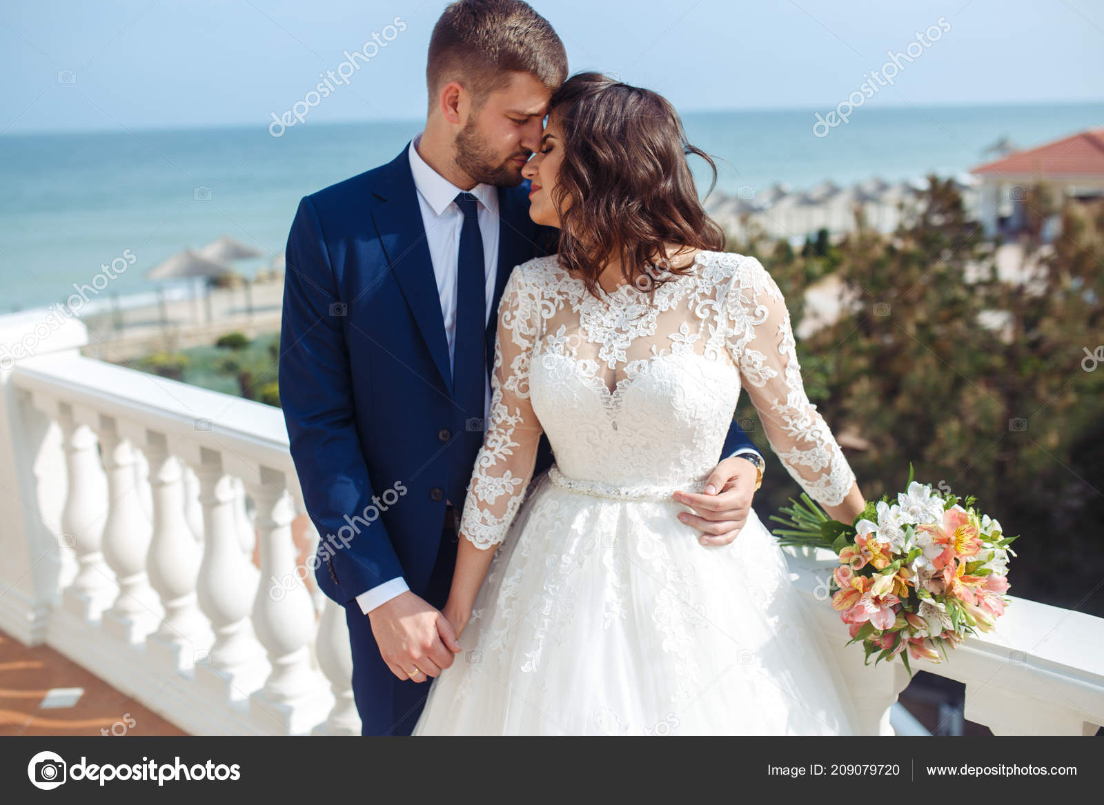 f8c60629fac Beautiful Bride and Groom enjoy each other on the background of the ocean.  happy romantic young couple celebrating their marriage.