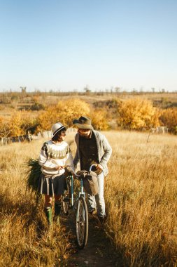 Lovely hipster couple with bike. Couple wearing beautiful hats and sweaters. Lifestyle, happy couple of two play on a sunny day in the park. The concept of youth, love and lifestyle. Sunset in autumn