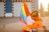 Krásná africká americká lesbická dívka s duhovou vlajkou LGBT při západu slunce. Mladá kudrnaté vlasy žena pózuje s Igbt pýchou vlajky.