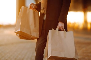 Shopping bags in the hands at sunset. Hand of young man with paper bags with purchases. Consumerism, purchases, shopping, black friday, lifestyle concept.