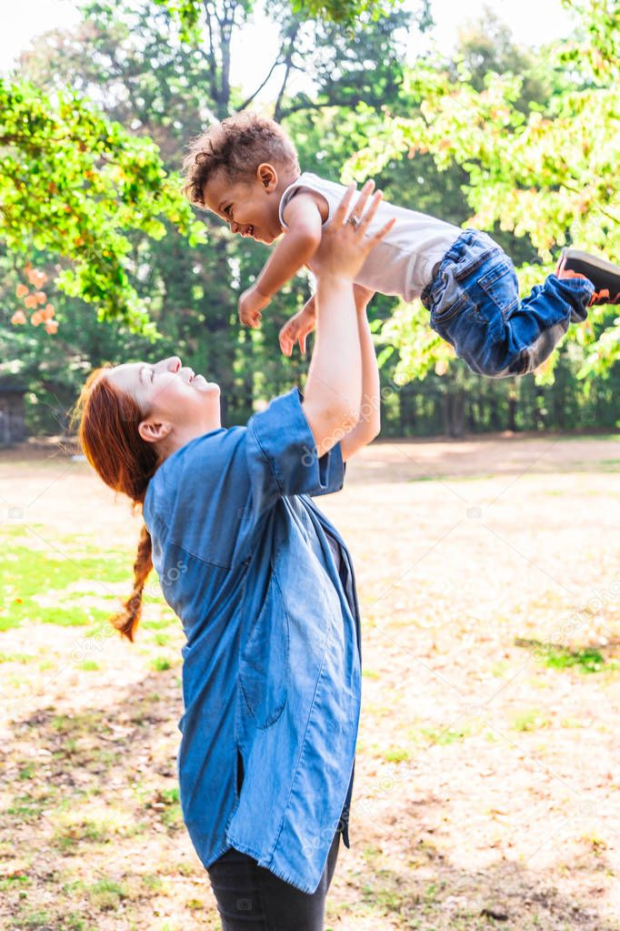 Mother tossing up son for fun in park in sunny day