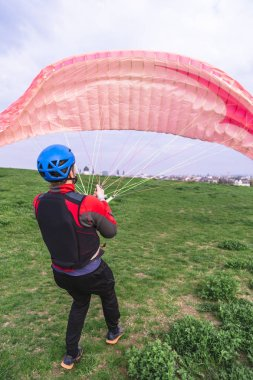 Man with paraplane starting to fly from hill top