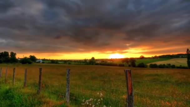 a View of The Beautiful Sunset in Cloudy Weather. on the Big Field Grows Tall Grass. the Field Dividing Fence With Wooden Pillars and Steel Wires.