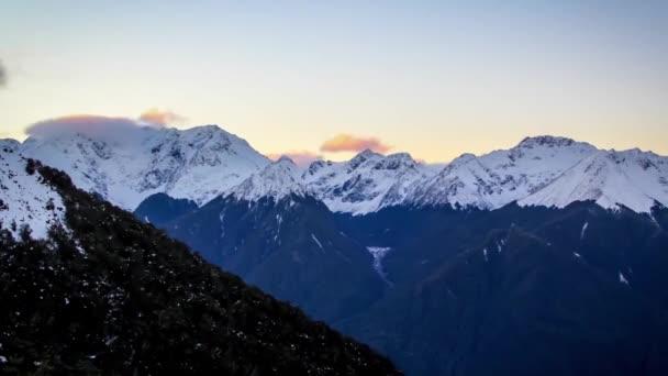 Zasněžené hory Nového Zélandu. Slunce. Na modrém nebi jsou vidět malé bílé mraky.