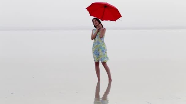 elegante Frau im Kleid am Strand mit rotem Sonnenschirm. Meeresspiegelung und schöne Frau. schöne Frau am Strand, genießt den Sommerurlaub.