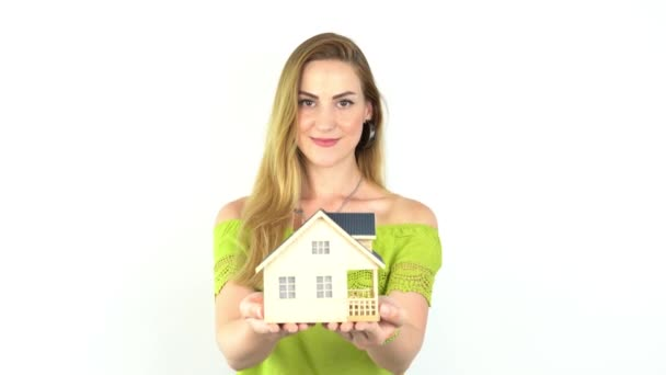 Ruce mladé ženy držící modelový dům, realitní pojištění a bankovní koncept.