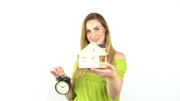 Hände junger Frau halten Musterhaus mit Wecker, Immobilienversicherung und Bankkonzept.