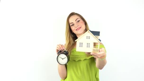 Ruce mladé ženy držící modelový dům s budíkem, realitní pojištění a bankovní koncept.