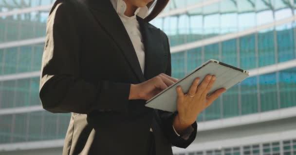 Zeitlupenvideo einer Geschäftsfrau, die ein digitales Tablet benutzt und surft und vor einem Bürogebäude steht