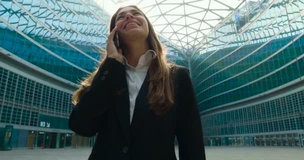 Slow-Motion-Video von der Geschäftsfrau im vollständigen Anzug telefonieren mit Handy im Freien im modernen Glasbau glücklich