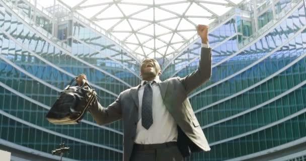 úspěšné šťastný africké obchodní muž na moderní budova ze skla, slow motion videa