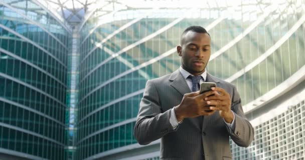 african business man at modern glass building using mobile phone, slow motion video