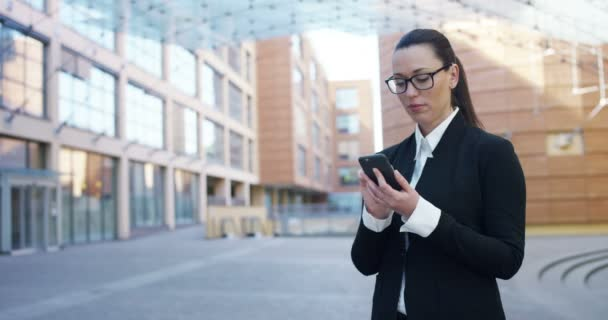 videó a üzletasszony, szemüveg, mobiltelefon használata utcában modern irodaház