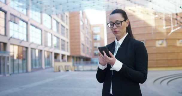 video of business woman using mobile phone in street at modern office building