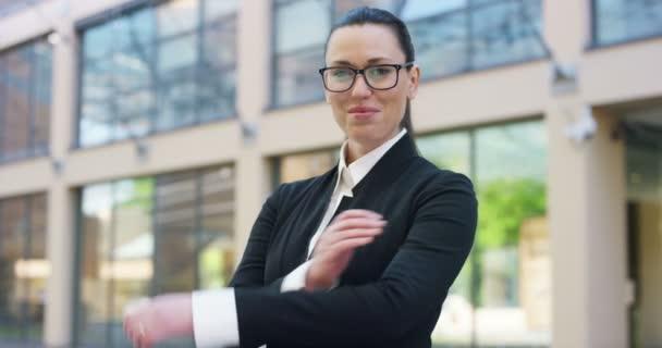 zpomalené video obchodních žena pózuje na kameru s rukama zkříženýma a stojící venku na stavební sklo