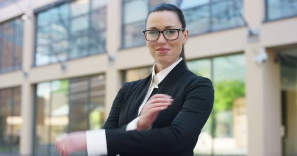 slow motion video of beautiful business woman posing on camera with arms crossed and standing outdoors at glass building