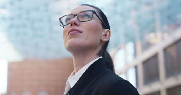 slow motion video of looking around business woman standing outdoors at glass building