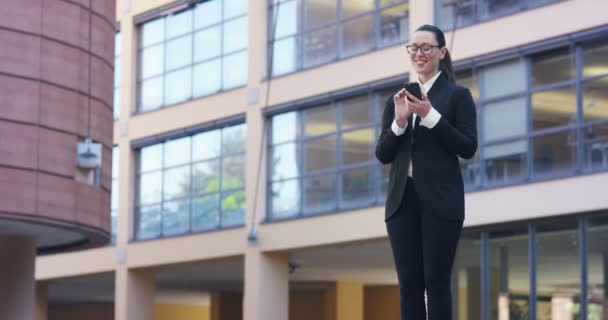 video of brunette woman in full suit using mobile phone while standing outdoors at modern glass building