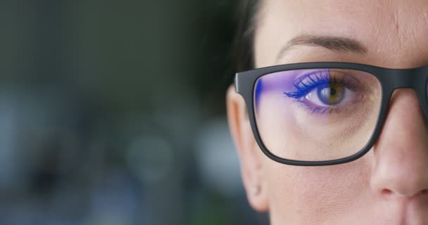 slow motion, macro video of woman face wearing glasses and looking at camera, cropped image of face