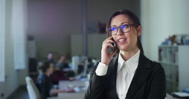 Zeitlupenvideo einer Geschäftsfrau, die im Büro mit Menschen im Hintergrund auf dem Handy spricht