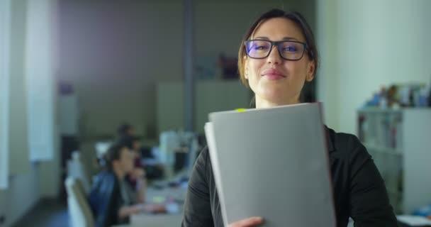 zpomalené video z úspěšného podnikání žena hospodářství složky, stojící v místnosti úřadu s kolegy na rozmazané pozadí
