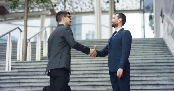 V městě dvě podnikatel si potřást rukou a úsměv než začnou spolupracovat na projektu. Koncepce: týmová práce, obchod, smlouvu, banka.