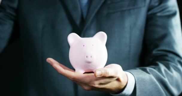 Muž, oblečený v obleku a kravatě, vloží peníze do prasátko. Koncepce: Důchod, úspory, investice, akumulace plán úspor pro studium vysoké školy