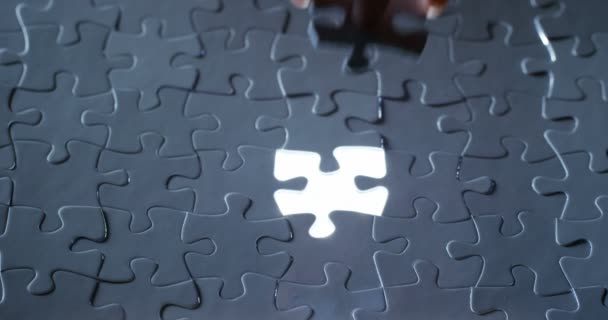 a hand completes a light black and white puzzle, concept of strategy, teamwork and finance world