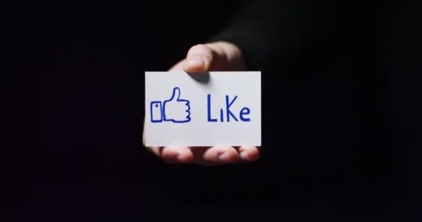 video, parziale vista della mano mostrando la tessera piccola carta con messaggio come e pollici in su