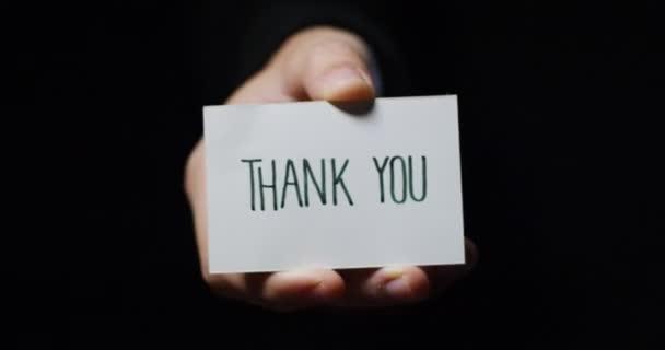 Video, Teilansicht der Hand zeigt kleine Papierkarte mit Dankesbotschaft